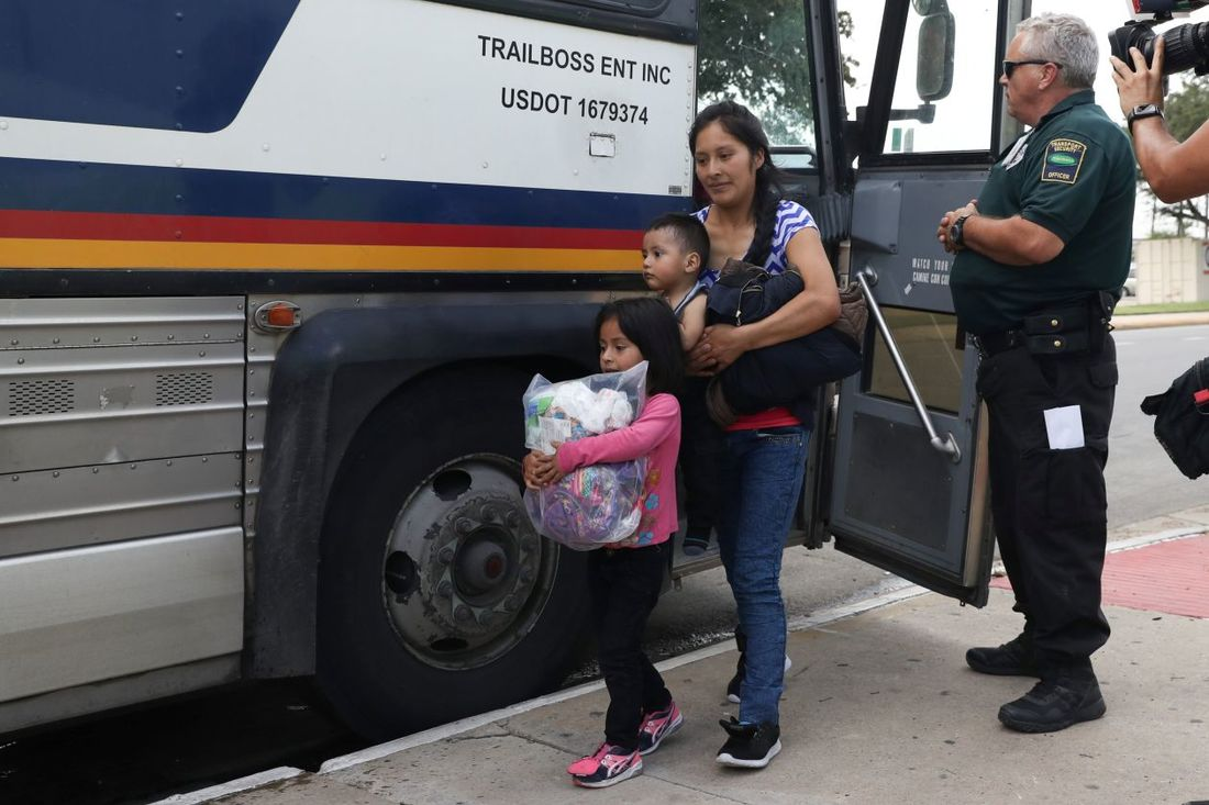 Migrant Mother and Her Children Exiting a Bus